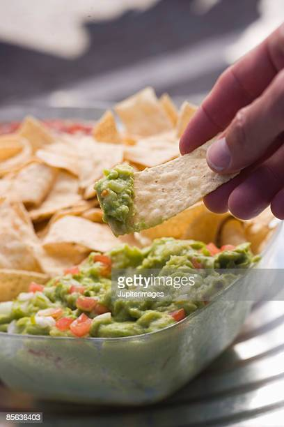 Hand with tortilla chips and guacamole