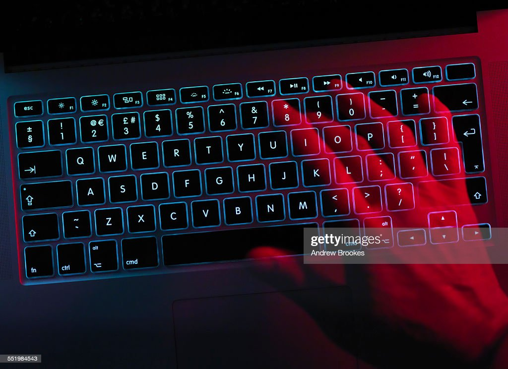 Hand working at laptop computer illustrating cyber crime : Stock Photo