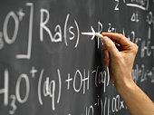 hand writing equation on blackboard