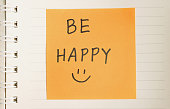 Be happy hand writing and hand draw smiley message on paper, light toned effect