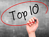 Man Hand writing Top 10 with black marker on visual screen. Isolated on grey. Business, technology, internet concept. Stock Photo