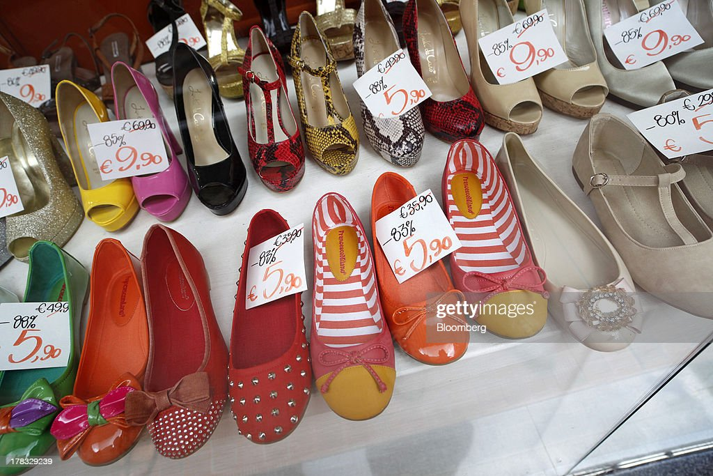 Hand written labels show the sale price in euros of shoes in the window display of a footware store in Pescara, Italy, on Thursday, Aug. 29, 2013. Italian consumer confidence rose this month more than economists expected as households grew optimistic amid expectations that the government would cut a property tax. Photographer: Marc Hill/Bloomberg via Getty Images