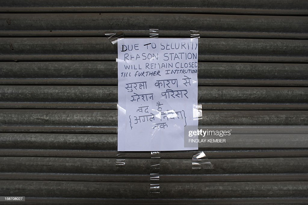 A hand written sign reading 'Due to security reason station will remain closed till further instructions' is affixed to a shutter a closed entrance to The Delhi Metro in Connaught Place in New Delhi on December 25, 2012. An Indian policeman injured in clashes during a protest over a gang-rape in New Delhi has died, a police spokesman said, as much of the city centre remains sealed off following the violence. Police barricaded roads leading to India Gate, an imposing war memorial in the centre of the city, that has become a hub of the protests by mostly college students. Many metro rail stations in fog-shrouded Delhi were also closed. AFP PHOTO/Findlay KEMBER