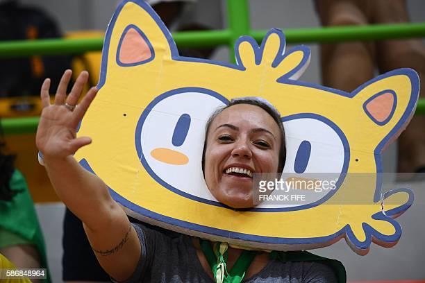 A handball fan sporting a cardboard cutout of the Rio 2016 mascot called Vinicius waves during the women's preliminaries Group B handball match...