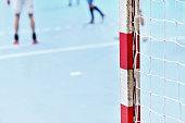 Detail shot with handball goalpost and players in the background