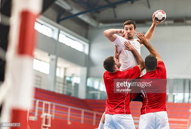Handball player jumping and shooting at goal.