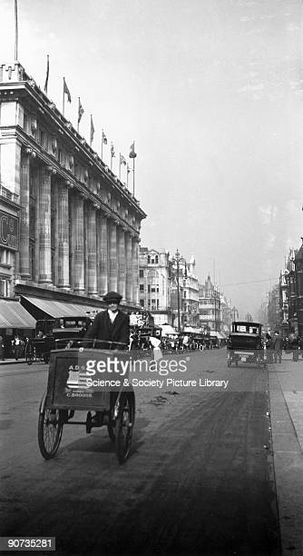 Handcart being pushed past Selfridges department store Oxford Street London c 1910s