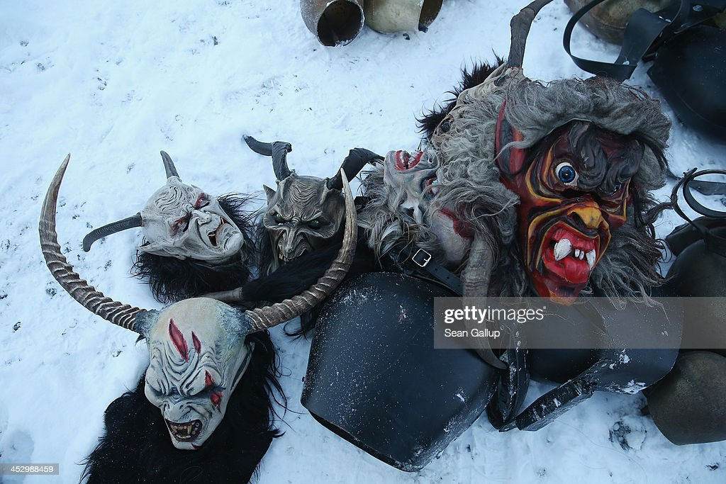 Hand-crafted Krampus masks lie in the snow as participants dress as the Krampus creature prior to Krampus night on November 30, 2013 in Neustift im Stubaital, Austria. Sixteen Krampus groups including over 200 Krampuses participated in the first annual Neustift event. Krampus, in Tyrol also called Tuifl, is a demon-like creature represented by a fearsome, hand-carved wooden mask with animal horns, a suit made from sheep or goat skin and large cow bells attached to the waist that the wearer rings by running or shaking his hips up and down. Krampus has been a part of Central European, alpine folklore going back at least a millennium, and since the 17th-century Krampus traditionally accompanies St. Nicholas and angels on the evening of December 5 to visit households to reward children that have been good while reprimanding those who have not. However, in the last few decades Tyrol in particular has seen the founding of numerous village Krampus associations with up to 100 members each and who parade without St. Nicholas at Krampus events throughout November and early December.