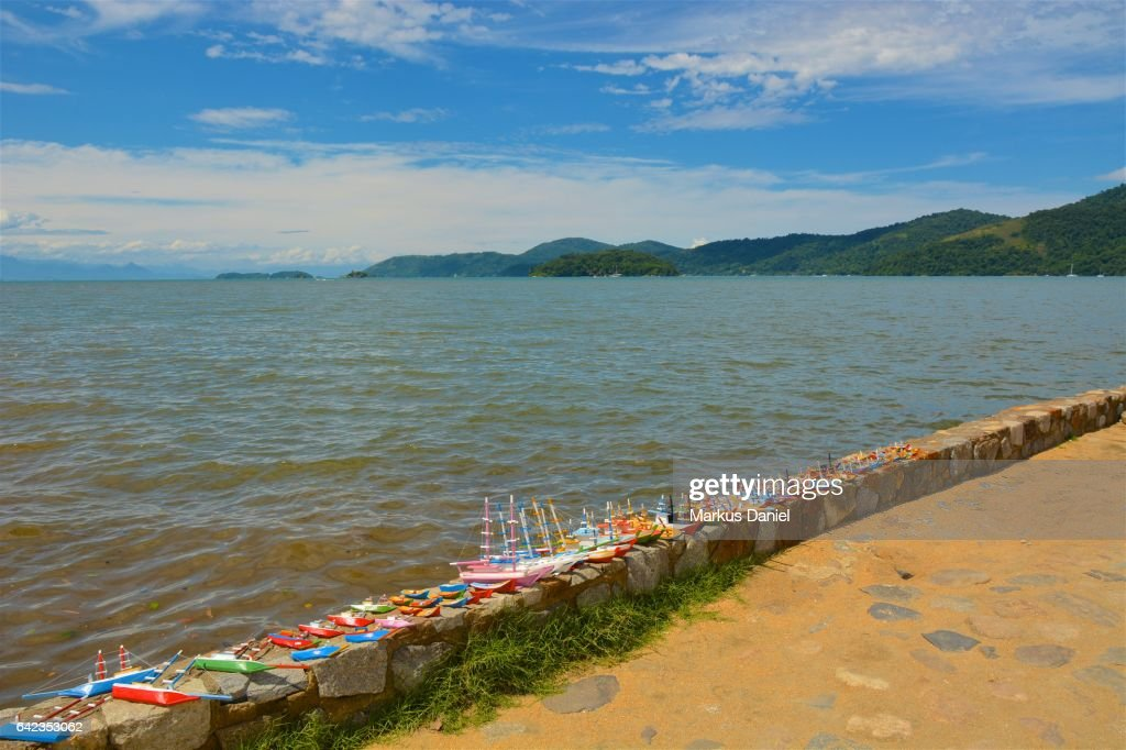 Handcrafted wood boats as souvenirs and the bay of Paraty, Rio de Janeiro : Stock Photo
