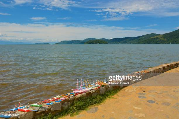 Handcrafted wood boats as souvenirs and the bay of Paraty, Rio de Janeiro