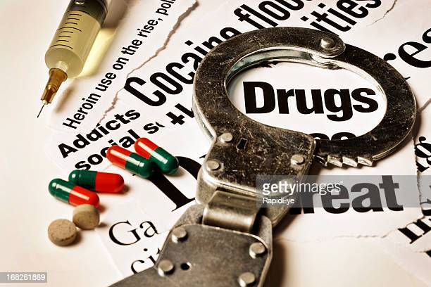 Handcuff frames drugs headline; hypodermic, tablets and capsules rest alongside