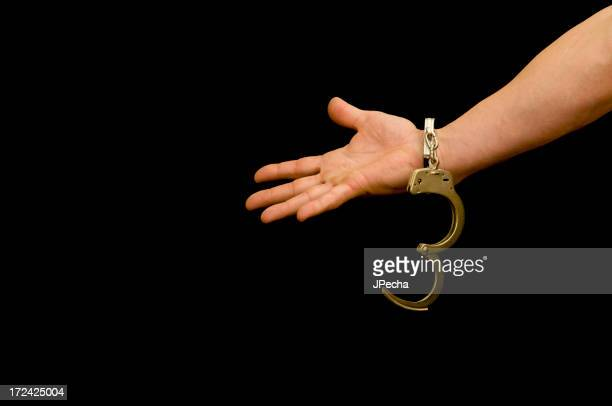 Handcuffed arm, Reaching out over black background