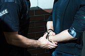 Dangerous and scary criminal is handcuffed by a policeman