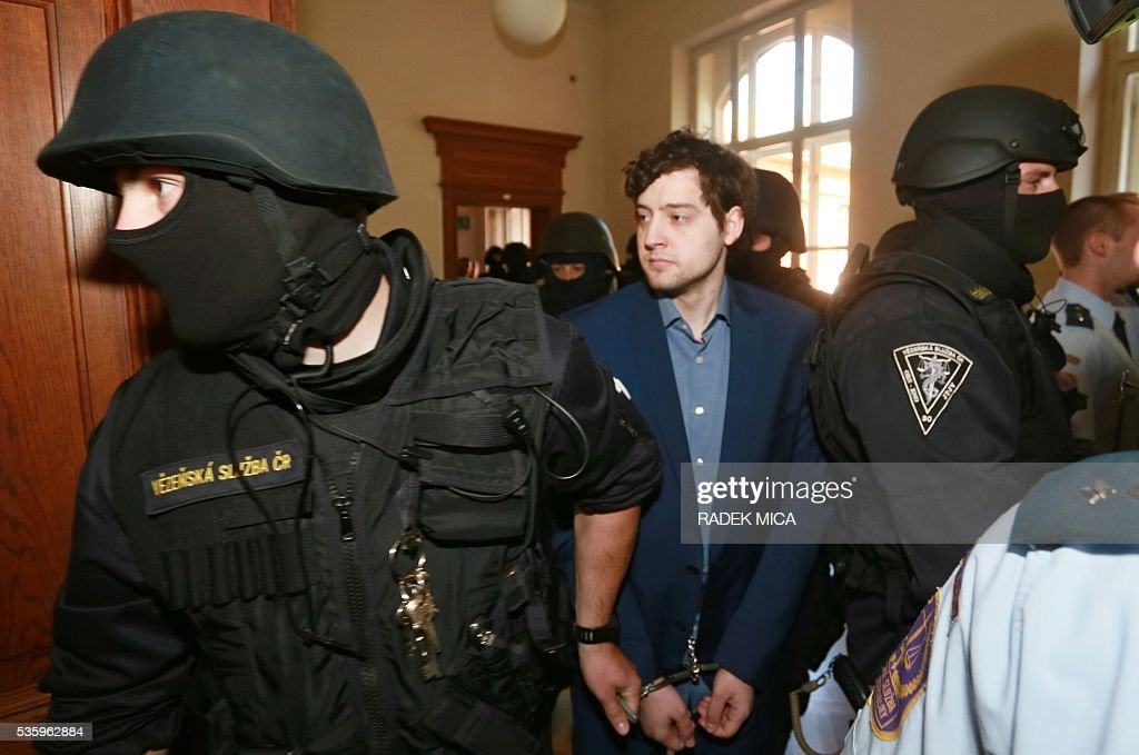 Handcuffed defendant Kevin Dahlgren (C) charged with quadruple murder is escorted to the courtroom for his trial on May 31, 2016 in Brno, Czech Republic. The US-citizen is accused of killing four of his relatives in the Czech Republic and then trying to incinerate their bodies. Kevin Dahlgren was extradited to the Czech Republic in 2015 after fleeing to the United States following the killings of his cousin, her husband and the couple's two sons. / AFP / Radek Mica