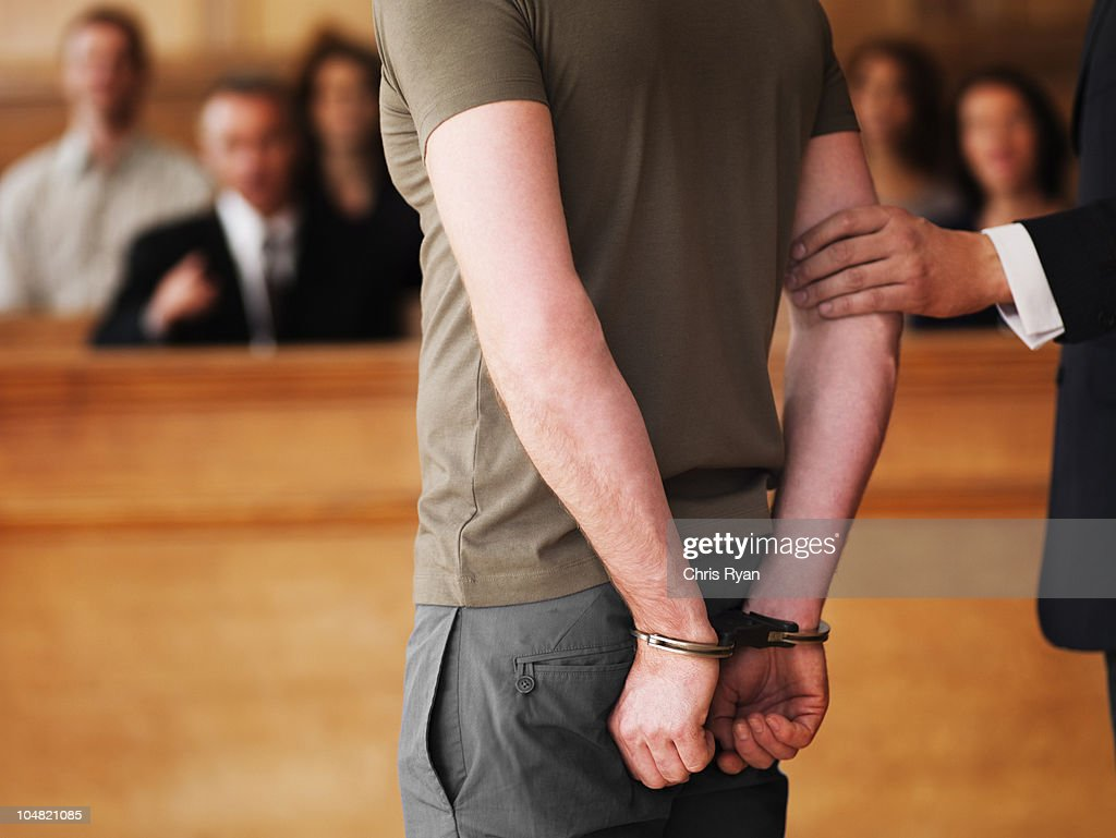 Handcuffed man standing in courtroom : Stock Photo