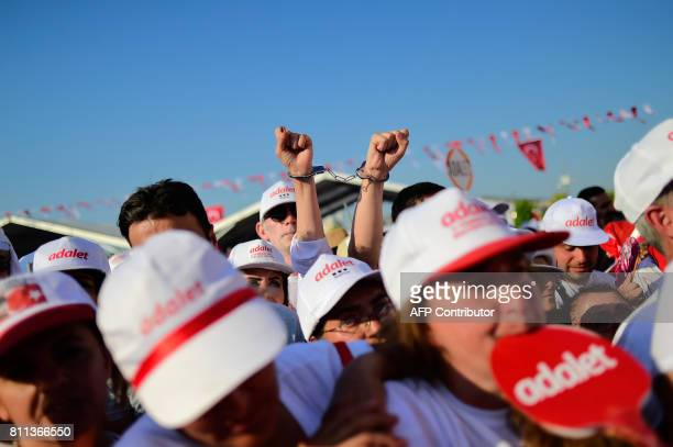 A handcuffed person gestures as Turkey's main opposition Republican People's Party leader Kemal Kilicdaroglu waves to supporters during a rally on...