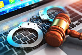 Creative abstract cyber crime, online piracy and internet web hacking concept: 3D render illustration of the macro view of metal handcuffs and wooden judge mallet, gavel or hammer on laptop notebook c