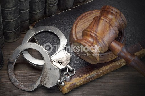 Handcuffs, Judge Gavel And Old Law Books On Wooden Table : Stock Photo