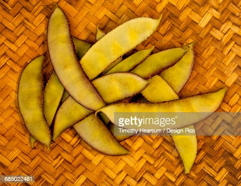 A handful of a tropical variety of peapods from a local farmers market rest on a woven mat on the Big Island : Stock Photo