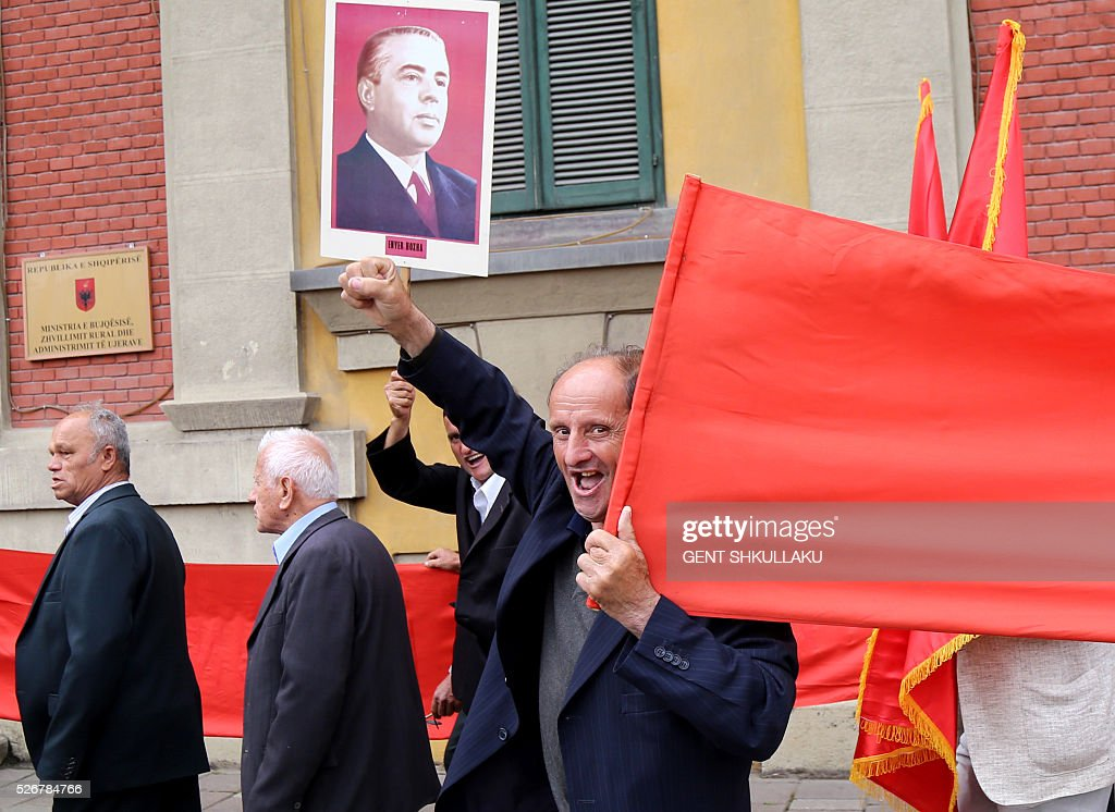 A handful of Albanian communists shout slogans holding a portrait of late Albanian communist dictator Enver Hoxha during a May Day march in Tirana on May 1, 2016. / AFP / GENT