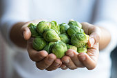 Woman showing Brussels sprout.