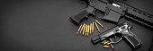 9mm handgun with ar15 rifle and ammunition on dark background with copy space
