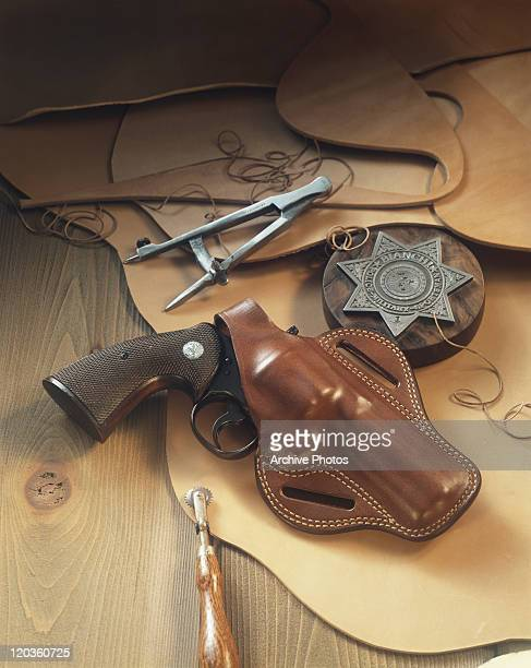 Handgun with badge on leather, close-up