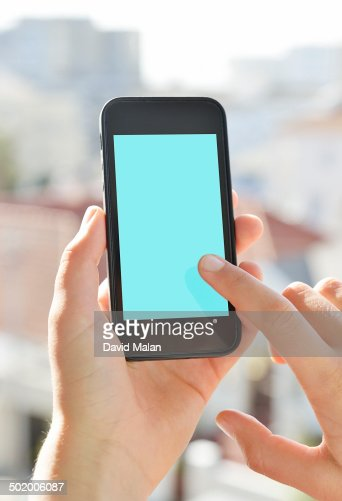 Handheld mobile device being used outdoors