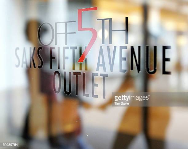 A handholding couple is reflected in signage for Off 5th Saks Fifth Avenue Outlet store at Old Orchard shopping center May 27 2005 in Skokie Illinois...