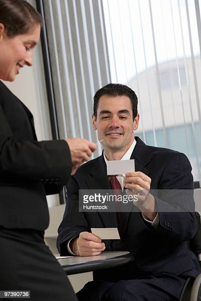 Handicapped businessman showing a visiting card to a businesswoman