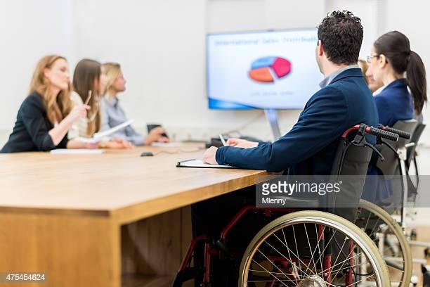 Minusválidos Hombre de negocios sentado en Wheelchai en reuniones de negocios