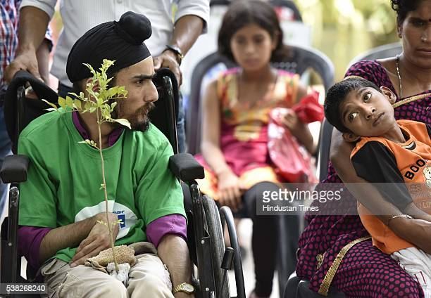 Handicapped children marching on wheelchair with saplings in their hands near 'India Gate' and adopting the saplings by planting them on the occasion...