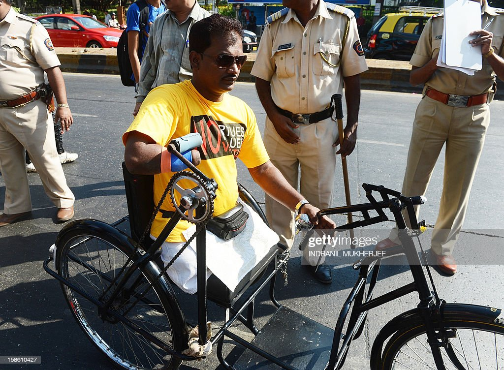 A handicapped Indian protester moves past police during a demonstration against Swiss drug manufacturer Novartis, outside their offices in Mumbai on December 21, 2012. Demonstrators including cancer patients were protesting against the potential impact of the company's legal battle in India. Novartis is engaged in a legal battle over a part of the country's patent law that led to the company being denied a patent by an Indian court on their cancer drug 'Gleevec'.
