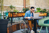 Smiling young handicapped man using laptop at cafe