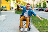 Laughing young positive handicapped man in a wheelchair