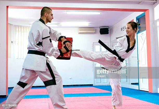 Handicapped martial arts trainee kicks punching bag