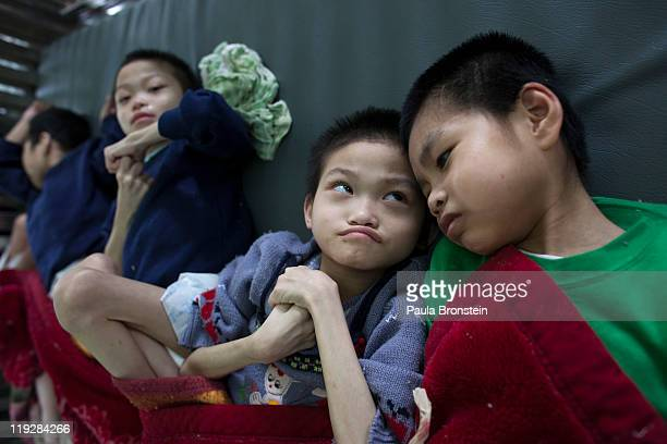 Handicapped orphans rest after eating lunch at the Ba Vi orphanage March 15 in Ba Vi Vietnam There are around 125 children who are cared for by...