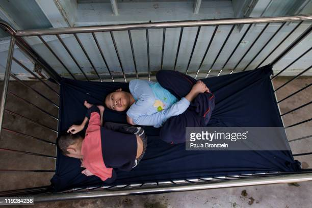 Handicapped orphans rest in a crib at the Duc Son Pagoda March 9 in Hue Vietnam There are 15 handicapped children amongst the 190 orphans most are...