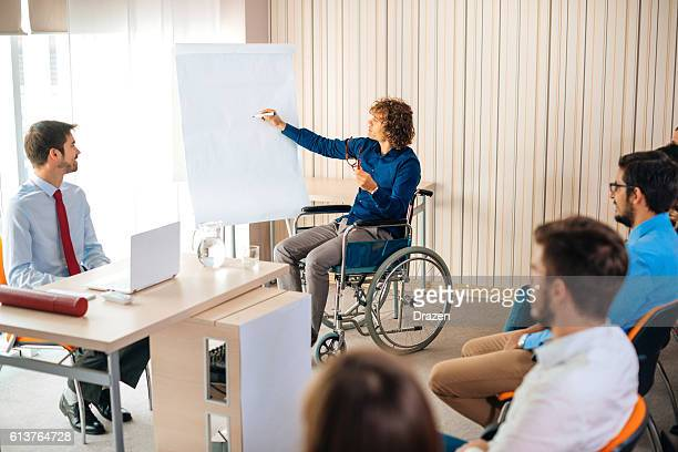 Handicapped person on seminar writing on flipchart