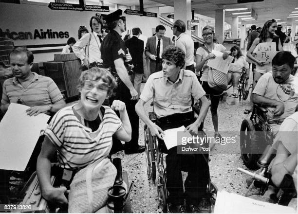 Handicapped persons gave a cheer after their spoksman Mark Johnson center announced that American Airlines had agreed to send an executive to meet...