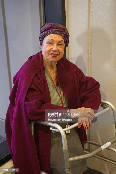 Handicapped woman with walker seated at window smiling