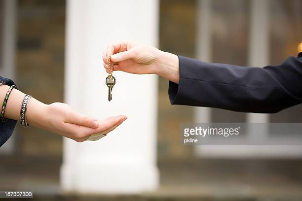 handing keys over in front of house