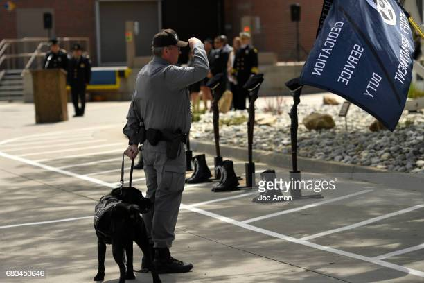 K9 handler Deputy Truman Aumiller salutes as the Denver Sheriff's Department hold a memorial ceremony for DSD officers who have died in the line of...