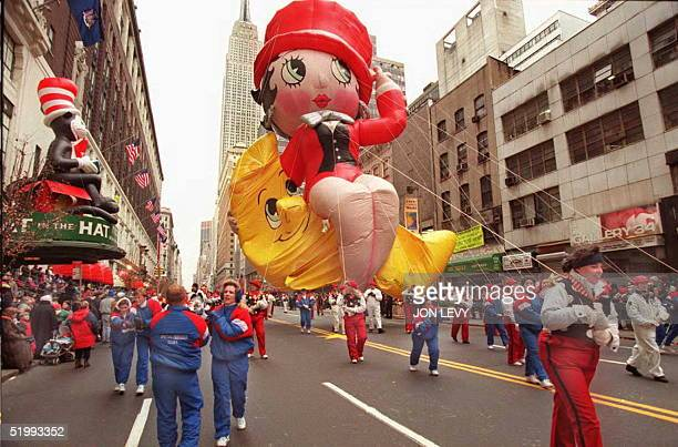 Handlers pull the Betty Boop balloon past Macy's department store with the Empire State building in the background 23 November during the 69th annual...