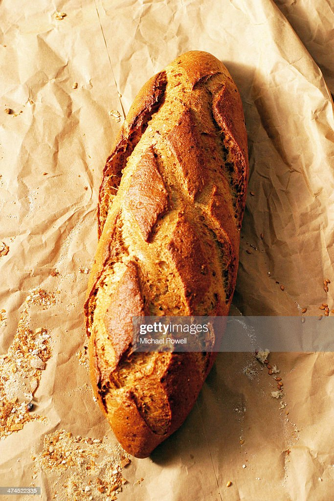 Handmade artisan French bread loaf on brown pape : Stock Photo