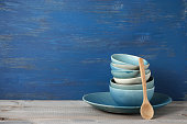 Stack of handmade blue ceramic bowls and wood spoon on rustic wooden table against blue painted wooden wall.