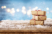 Image of handmade gift boxes over snowy wooden table