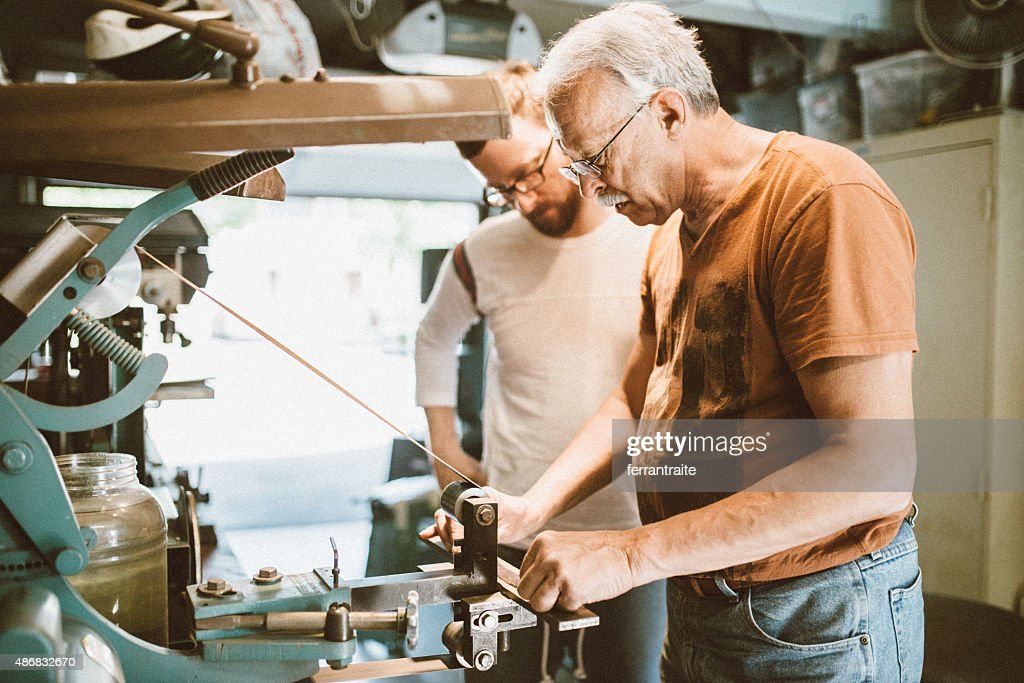 Father and son in workshop making custom knifes