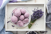 Handmade lavender bath bombs and lavender flowers in white tray, top view