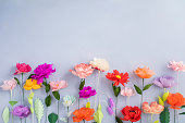 Colourful handmade paper flowers on light blue background with copyspace